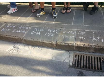 Una scritta su un marciapiede di Fermo durante la manifestazione dei centri sociali